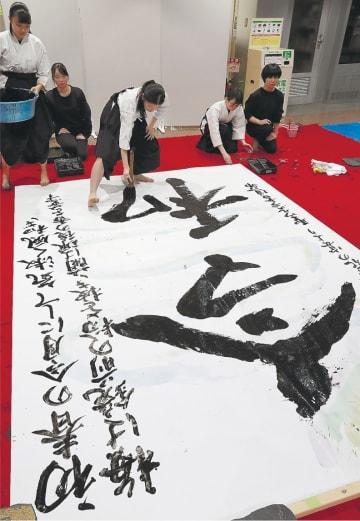 全身を使って文字を書き上げる聖ウルスラ学院英智高の書道部員=1日午後1時20分ごろ、仙台市若林区役所