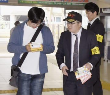 情報提供を求めるチラシを配布する捜査員=2日午前、愛知県豊田市