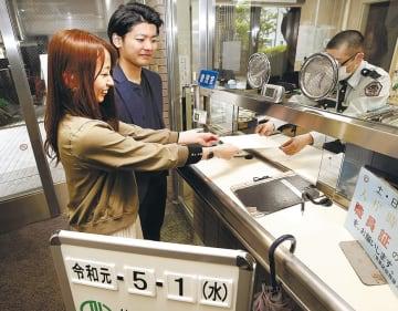 守衛に婚姻届を手渡すカップル=1日午前9時ごろ、仙台市青葉区役所