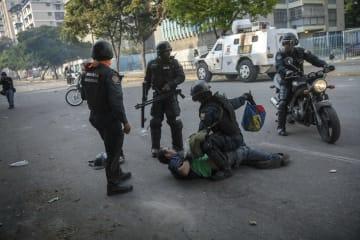 ベネズエラの首都カラカスで、反政府デモ参加者を取り押さえる警察官ら=1日(AP=共同)