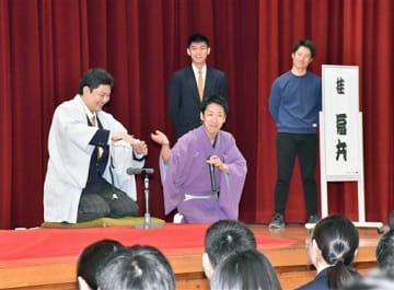 桂福丸さん(中)に教わり、扇子をとっくりに見立て酒を飲む演技に挑む生徒ら=26日、百石高校