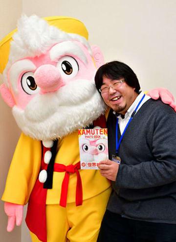 自身の写真集にご満悦のかむてんと、企画編集に当たった高橋諒さん=新庄市役所