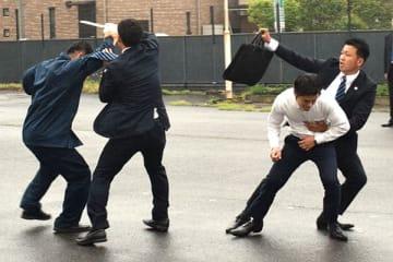 刃物を持って襲撃した犯人(左)から保護対象者(右から2人目)を守る県警の身辺警戒員=さいたま市北区の県警察学校