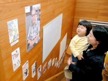 加古里子さんの写真や自画像に見入る来場者=5月2日、福井県越前市のかこさとしふるさと絵本館