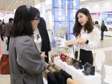 小売店と国外ECサイト業者の商談会で婦人向けバッグを紹介する韓国人の女性経営者(右)=3月、ソウル(共同)