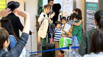 見送りに手を振って別れを惜しむ帰省客たち=3日午前、宮崎市・宮崎ブーゲンビリア空港