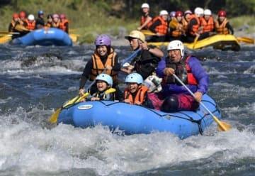 球磨川の急流で水しぶきを浴びながらラフティングを楽しむ観光客ら=3日午後、球磨村(後藤仁孝)