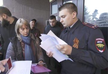 3日、ウクライナ東部ドネツクで地元住民からロシア国籍の申請書類を受け取る親ロシア派「ドネツク人民共和国」の移民局の男性(右)(タス=共同)