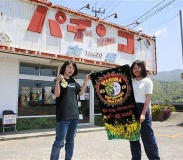 「WANIMA」の聖地となっているパチンコ店跡で、記念撮影をする県外から訪れたファン=3日、天草市