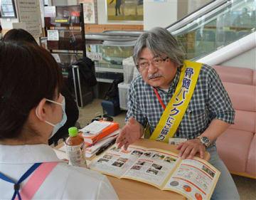 登録会を訪れたドナー登録希望者に、パンフレットを使いながら丁寧に説明する前田さん=4月24日、八戸赤十字病院
