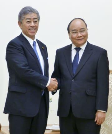 ベトナムのグエン・スアン・フック首相(右)と握手する岩屋防衛相=4日、ハノイ(共同)