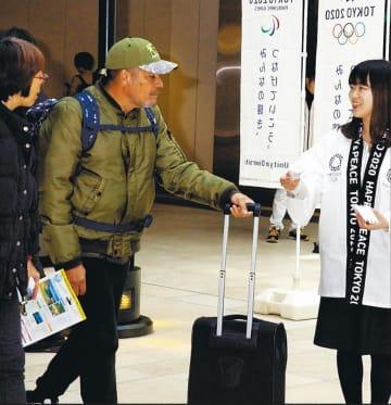 通行人に都市ボランティア募集をPRする県職員(右)=4月8日、JR仙台駅