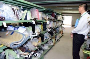傘やかばんといった落とし物が並ぶ鹿児島中央署の保管庫=鹿児島市の同署