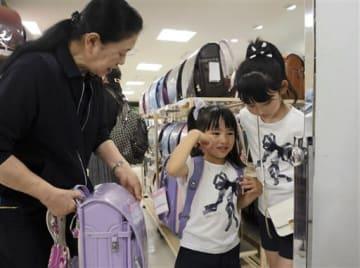 連休中、帰省した孫と一緒にランドセルを選ぶ来店客=熊本市中央区