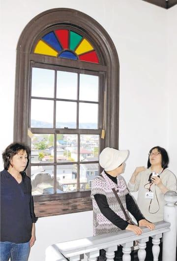 町並みを望む塔屋で、ガイド(右)の説明を聞く参加者