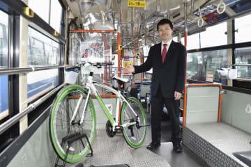 自転車を載せられる「サイクリングバス」の内部を紹介する函館バス営業課の伊藤龍一さん=4月、北海道函館市