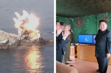 「飛翔体」が岩に命中し、その様子をモニターで見て喜ぶ朝鮮労働党の金正恩委員長(写真右、労働新聞から)