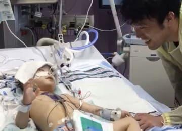 父親の呼び掛けに応じて手を上げる長岡璃空ちゃん=米アーカンソー小児病院(りくくんを救う会提供)