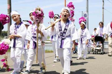 「花山」を担いで掛け声を響かせながら集落を歩く子どもたち=5月5日、福井県福井市栃泉町