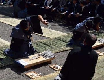 独特の所作でふなずしを切り分ける谷さん(左)と樋上さん=守山市幸津川町・下新川神社
