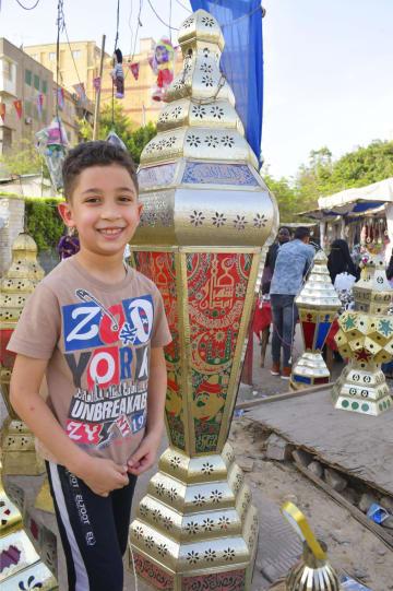 ラマダン中に飾るランプ「ファヌース」の横で笑顔を見せる少年=5日、カイロ(共同)