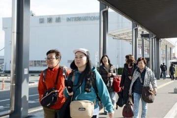 熊本空港国際線ビル近くの通路を歩く旅行者ら=3月、益城町