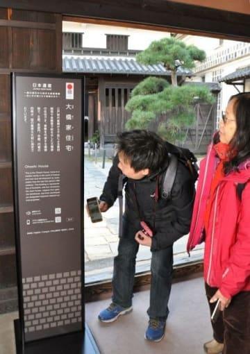 立て看板に表示されたQRコードにスマートフォンをかざす外国人観光客=大橋家住宅