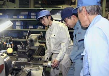 玉川工業のインターンシップで、担当者(手前)から作業の説明を受ける2人の男子高校生=3月、愛知県春日井市