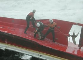 船体を固定し、船内の捜索を続ける特殊救難隊員=平成14年1月22日、鷲別岬付近