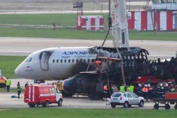 6日、モスクワ郊外のシェレメチェボ空港で事故機を調べる当局者ら(タス=共同)