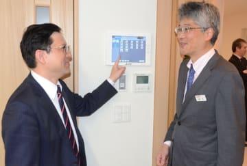 松下部長(右)から空調の集中コントローラーの説明を受ける米田社長