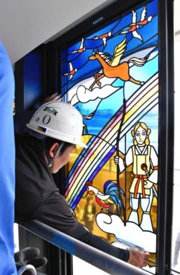 設置作業が進む藤城清治さん原画のステンドグラス=8日午後、宮崎市・宮崎ブーゲンビリア空港