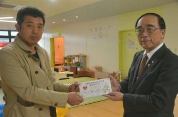 臼杵市の出生祝い品で商品券を受け取った吉成直人さん(左)と中野五郎市長