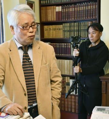 ロンドン漱石記念館の開館式典で、館長の恒松郁生さん(左)を撮影する梶岡潤一さん=8日、ロンドン郊外(共同)