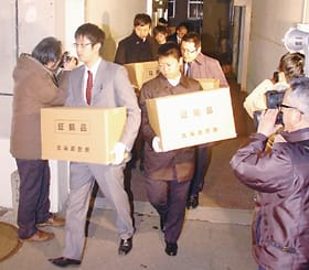 室蘭市発注の市営住宅改修工事を巡る贈収賄事件で、室蘭市役所を家宅捜索し、関係書類などを押収する道警の捜査員ら=平成24年2月23日、室蘭市役所