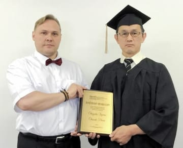 ペトリギン教授から盾を受ける岡崎さん(右)