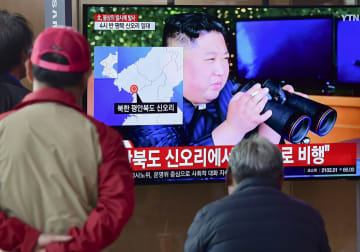 ソウル駅に設置されたテレビで、北朝鮮の飛翔体発射のニュースを見る市民=9日(共同)