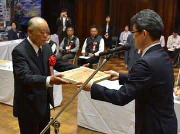 河野知事(右)から賞状を受け取る県地域づくり顕彰の受賞者=9日午後、県庁講堂
