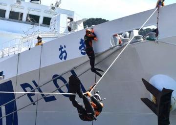 ロープを使って巡視船の船体へよじ登ったり、陸へ降下したりする潜水士たち(京都府舞鶴市西・舞鶴港第3埠頭)