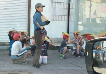 地震発生直後、ノートのような物で頭を守る子どもたち=10日午前8時49分、宮崎市江平東2丁目