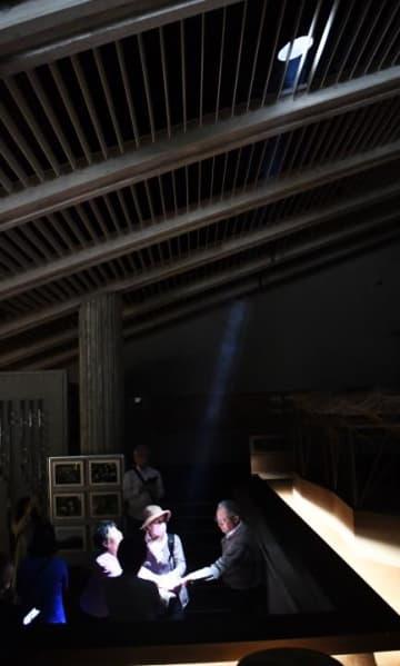 別子銅山記念館の天窓から差し込む光を手で受け止める来場者=9日正午ごろ、新居浜市角野新田町3丁目