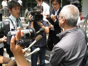 裁判員裁判で初の無罪判決が出た後、報道陣の取材に応じる裁判員を務めた男性(右)=2010年6月、千葉地裁前