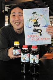 ご当地萌えキャラ「矢田川あゆか」をデザインしたしょうゆとクッキーをPRする阿瀬大典さん=道の駅「あゆの里矢田川」