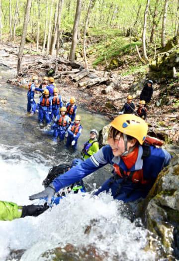 水しぶきを上げながらシャワークライミングを楽しむ生徒