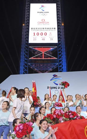 「開幕まで1000日」の文字が表示された2022年北京冬季五輪のカウントダウンのタイマーの前で盛り上がる若者ら=10日、北京(共同)