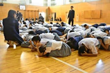 集会中に震度5弱の地震が発生し、床に伏せて揺れが収まるのを待つ児童たち=10日午前8時48分、宮崎市・宮崎大付属小
