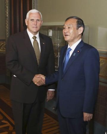 米ワシントンのホワイトハウスでペンス副大統領(左)と握手する菅官房長官=10日(在米国日本大使館提供・共同)