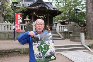 神社境内で、ポスターを手に催しをPRする奥野さん=亀岡八幡宮