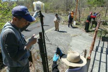 乱獲を防ぐため、市道に向けてビデオカメラを設置し、牧草地周辺にロープを張る地元住民ら=竹田市久住町