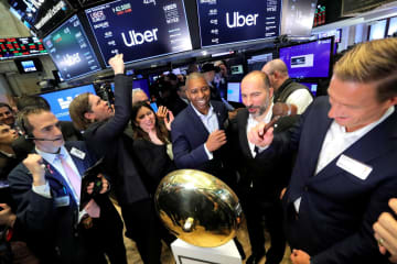 10日、米ニューヨーク証券取引所で上場を祝うウーバー・テクノロジーズの関係者ら(ロイター=共同)